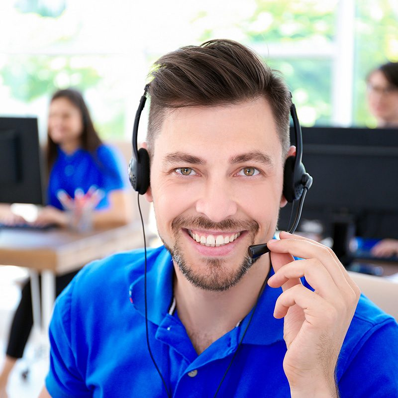 Male technical support operator with headset at workplace